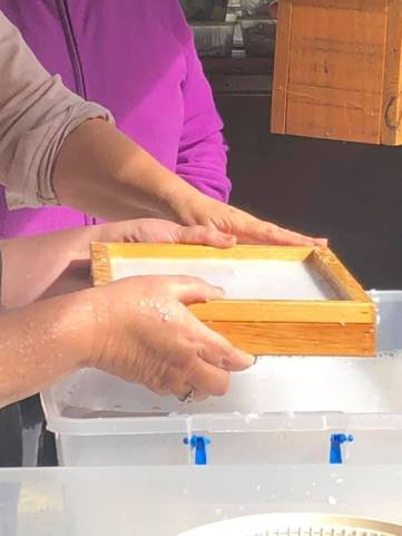 Papermaking: pulling pulp onto the frame