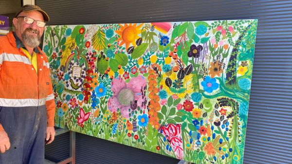 Geoff from the Dereel Mens Shed with 'In The Garden' community mural.